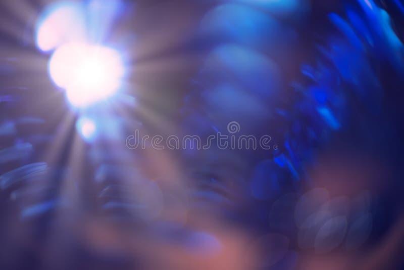 Les faisceaux lumineux pourpres et bleus de cru de bokeh brillent sur le fond foncé avec le copie-espace, nuance molle pourpre de image libre de droits