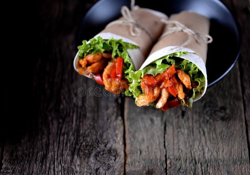 Les Fajitas avec le poulet, le poivre, oignon à une sauce tomate épicée, ont servi dans une tortilla image stock