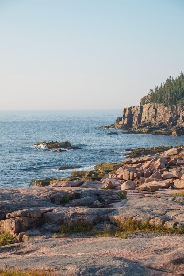 Les falaises de loutre à l'arrière-plan avec des dalles de granit rose bascule images libres de droits