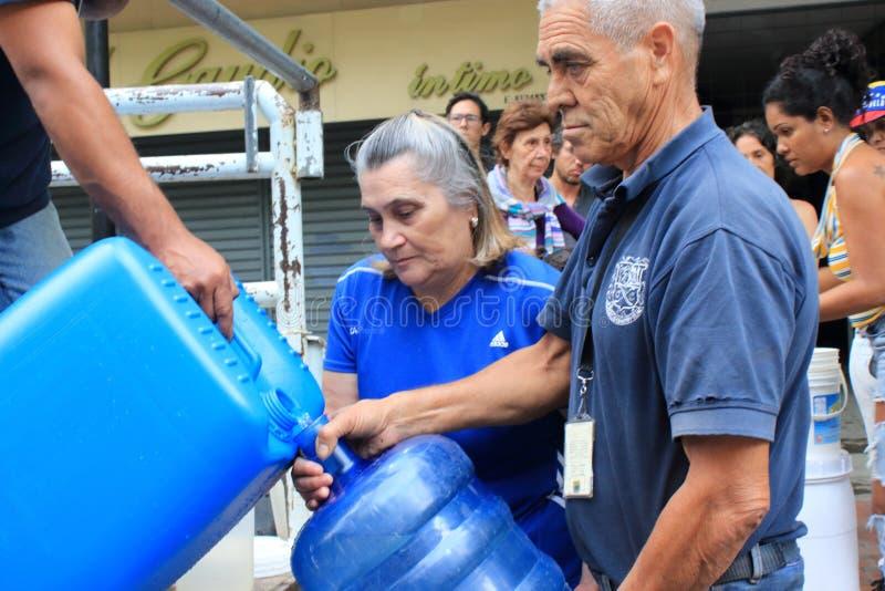 Les familles recueillies vers le haut des bouteilles en plastique pour les remplir de tuyaux flexibles arrosent à Caracas, Venezu photos libres de droits