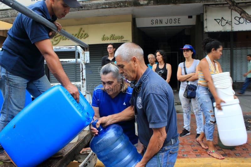 Les familles recueillies vers le haut des bouteilles en plastique pour les remplir de tuyaux flexibles arrosent à Caracas, Venezu photographie stock libre de droits