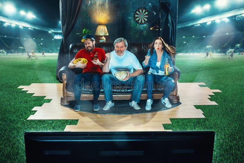 Les fans ardentes se reposent au sofa et à la TV de observation au milieu d'un terrain de football images stock