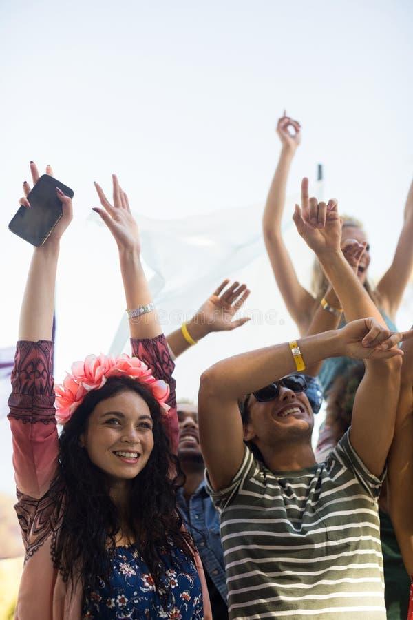 Les fans heureux avec des bras ont soulevé apprécier au festival de musique photos stock