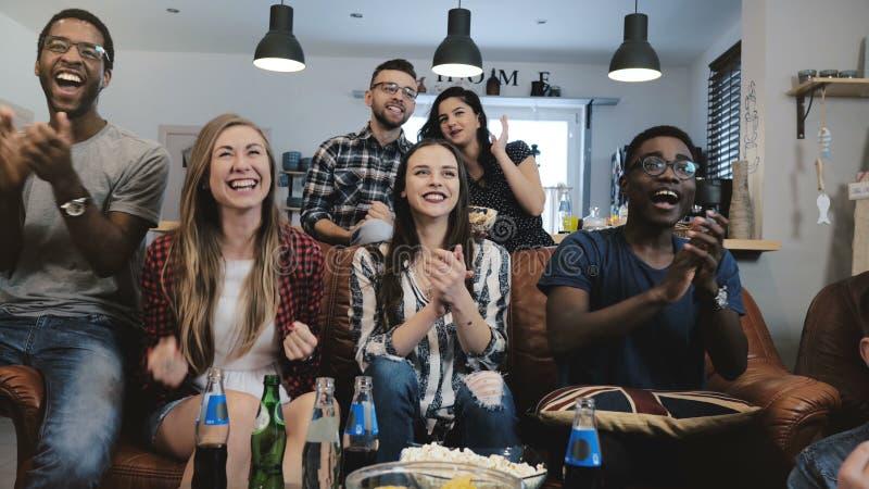 Les fans multi-ethniques deviennent folles célébrant le but à la TV Les défenseurs passionnés du football crient avec le mouvemen image libre de droits