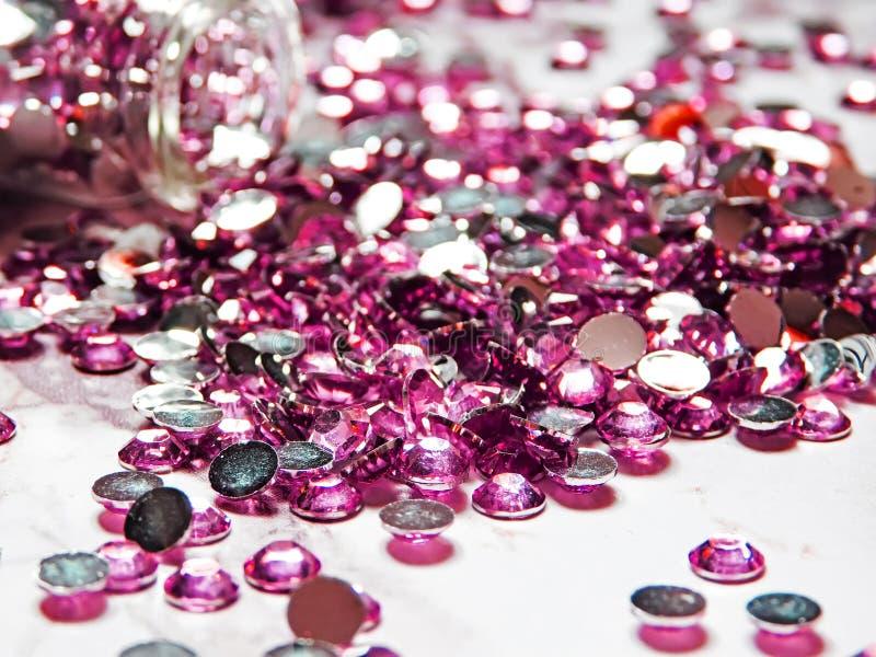 Les fausses pierres roses ont versé d'une bouteille en verre sur une table de marbre photo stock