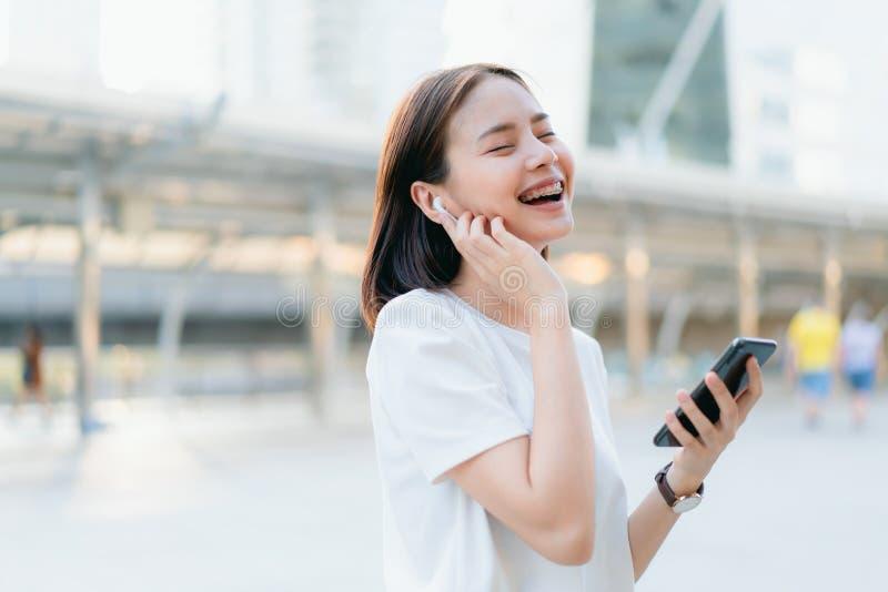 Les femmes écoutent la musique des écouteurs blancs Et employant le contact de mains pour employer de diverses fonctions photo libre de droits