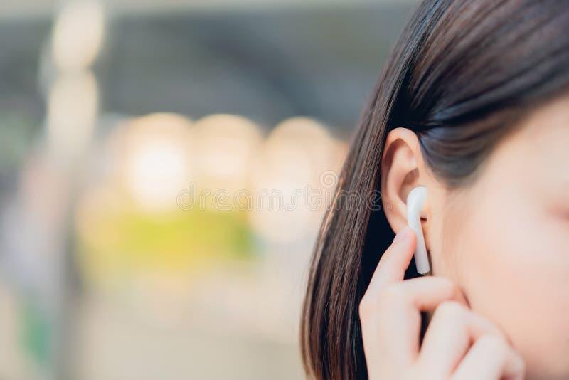 Les femmes écoutent la musique des écouteurs blancs Et employant le contact de mains pour employer de diverses fonctions photos libres de droits