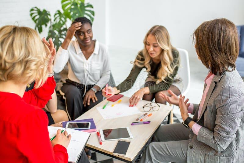 Les femmes africaines et caucasiennes se réunissent au studio, après stage de formation de divan image stock