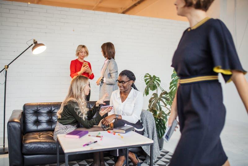 Les femmes africaines et caucasiennes se réunissent au studio, après stage de formation de divan photographie stock