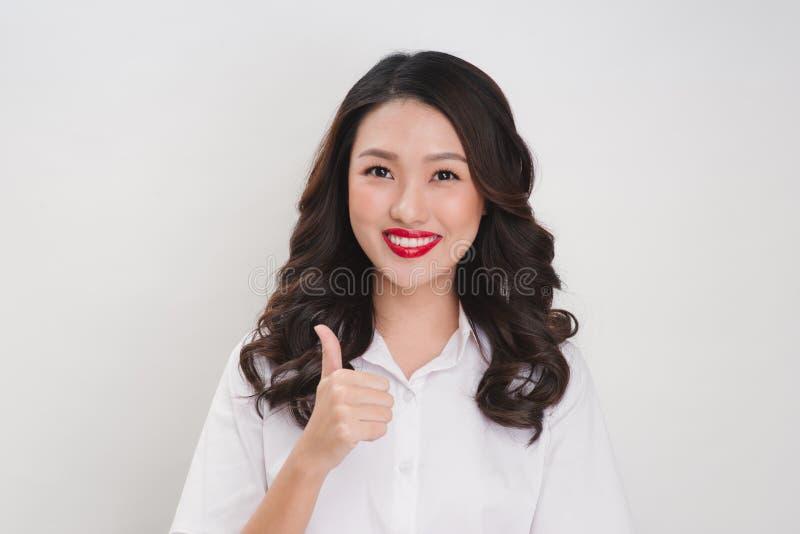Les femmes asiatiques d'affaires sourient et des coups vers le haut de signe de main pour le travail photos stock