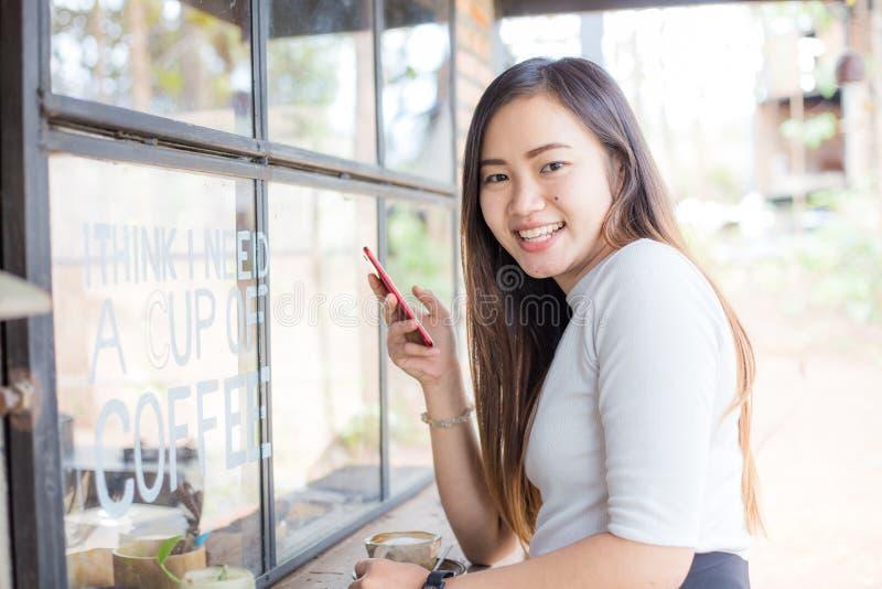 Les femmes asiatiques d'affaires textotant au téléphone intelligent dans le coffe moderne font des emplettes photographie stock