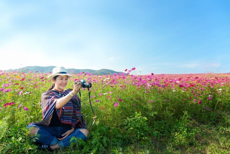 Les femmes asiatiques de voyageur s'asseyant et prennent une photo en fleur de cosmos de contact de gisement et de main de fleur, image libre de droits