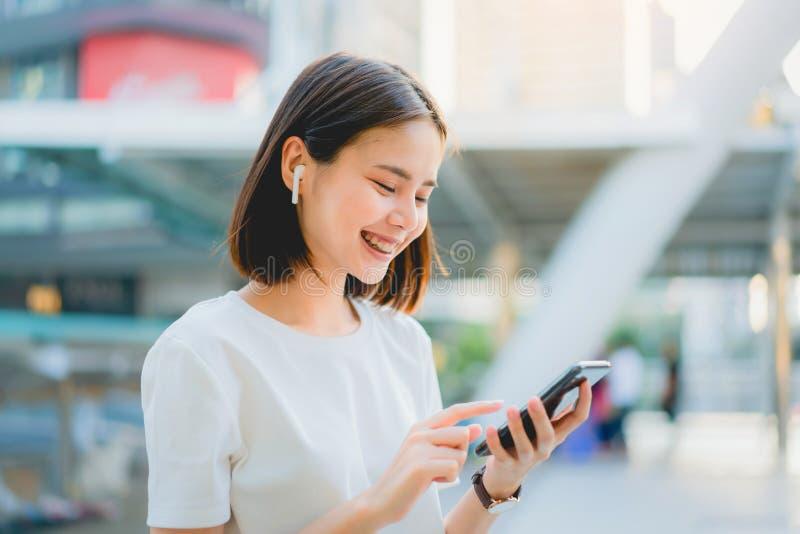 Les femmes asiatiques du sourire heureux écoutent la musique des écouteurs blancs photo libre de droits