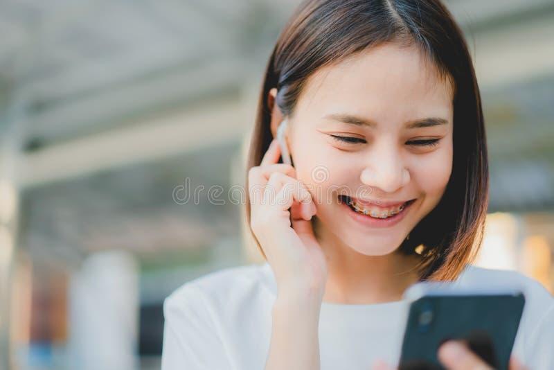 Les femmes asiatiques du sourire heureux écoutent la musique des écouteurs blancs photo stock
