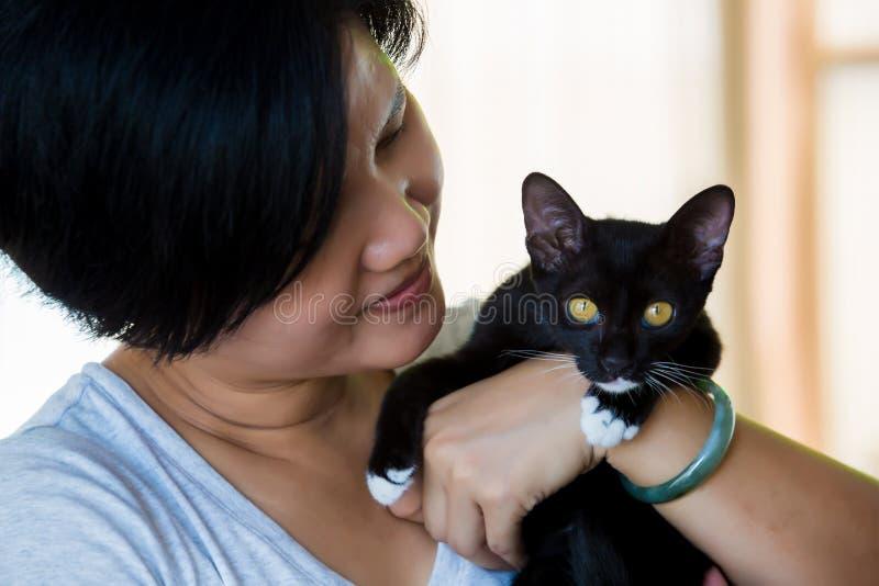 Les femmes asiatiques portent un mignon chat noir photo stock