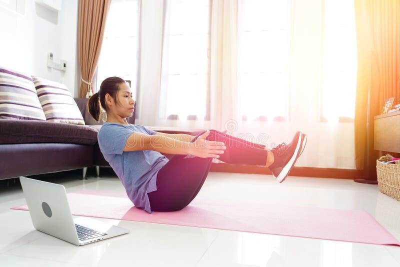Les femmes asiatiques s'exercent faisant la séance d'entraînement d'ABS de v-UPS à la maison photos libres de droits