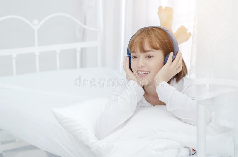 Les femmes asiatiques se sont reposées dans la chambre Elle était souriante et écoutante la musique photos stock