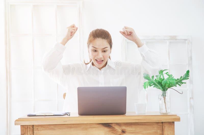 Les femmes asiatiques travaillent avec les ordinateurs portables gris sur le sofa dans la chambre pendant le matin photo stock