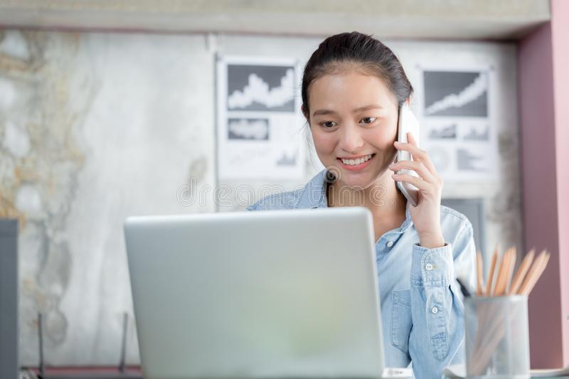 Les femmes asiatiques utilisent des ordinateurs portables et t?l?phonent dans le bureau image libre de droits