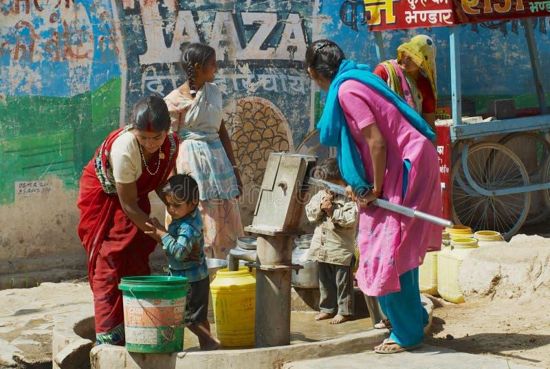 Les femmes avec des enfants pompent l'eau dans des récipients en plastique avec une pompe à main à la rue dans Orchha, Inde photographie stock libre de droits
