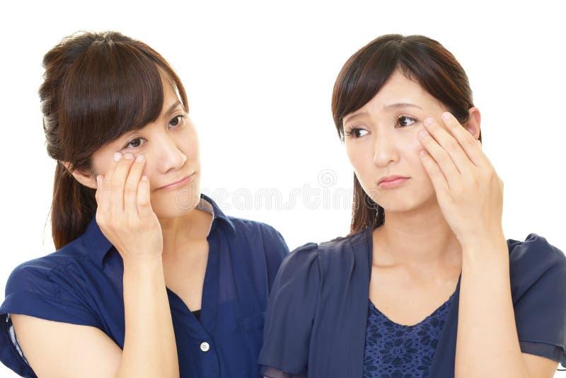 Les femmes bouleversées a des problèmes de peau images libres de droits