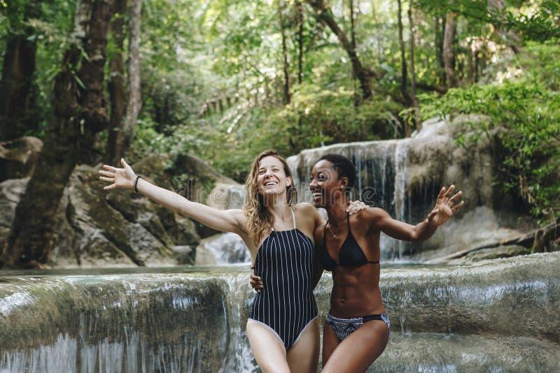 Les femmes couplent apprécier la cascade images stock