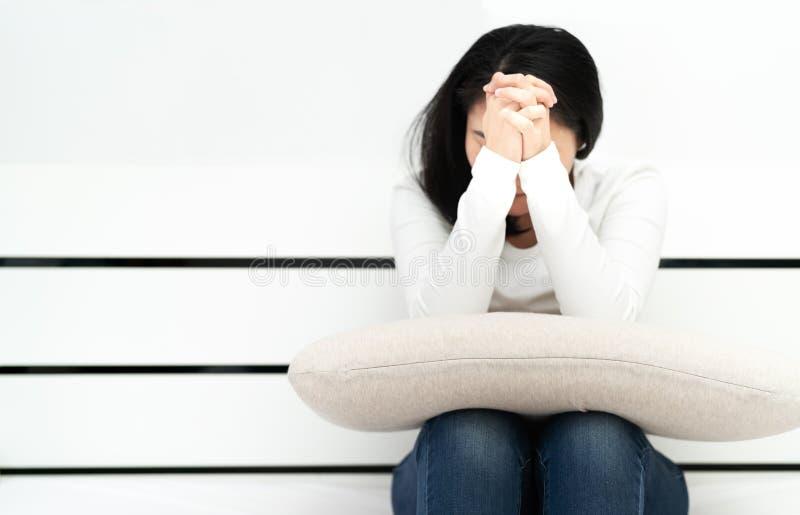 Les femmes déprimées s'asseyant et prient dans la chambre, seule, tristesse, concept émotif image stock