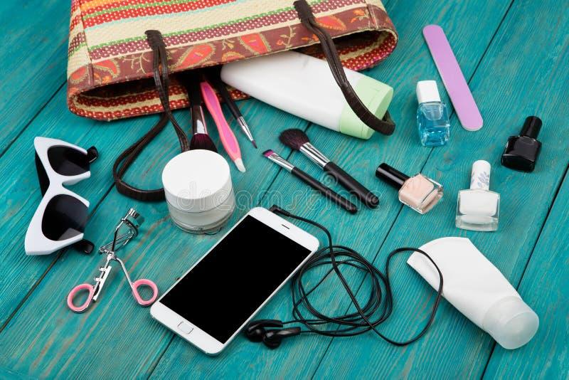 les femmes d'été ont placé avec le sac de paille, smartphone avec des écouteurs, le soleil photo stock