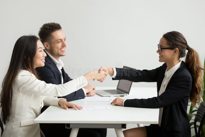 Les femmes d'affaires diverses de sourire se serrent la main lors de la réunion de groupe, affaire images stock