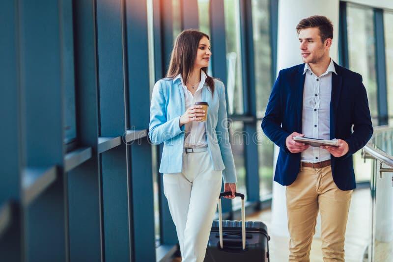 Les femmes d'affaires tiennent le voyage de bagage sur le voyage d'affaires photo stock