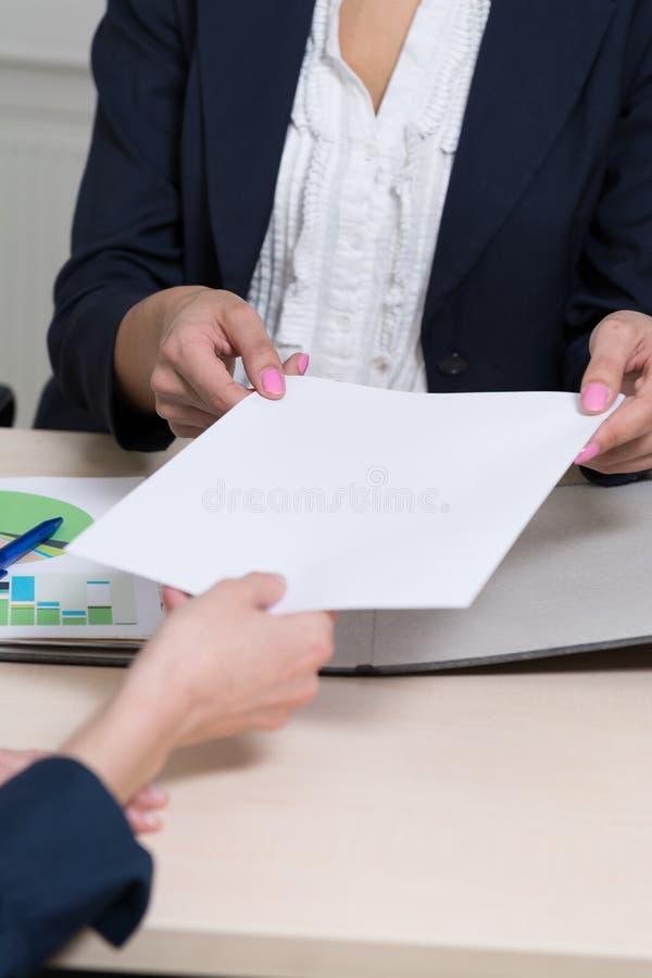 Les femmes d'affaires une remet un document photos libres de droits
