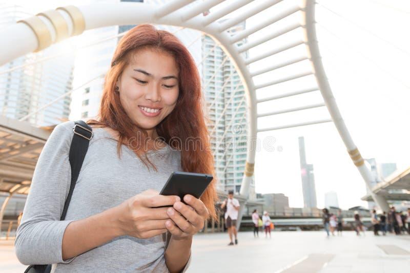 Les femmes de beauté sourient type mobile message de smartphone d'utilisation photo libre de droits