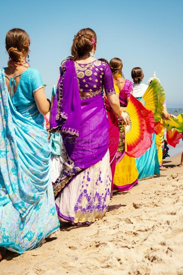 Les femmes de krishna de lièvres dans des robes colorées marchent sur la plage photo stock