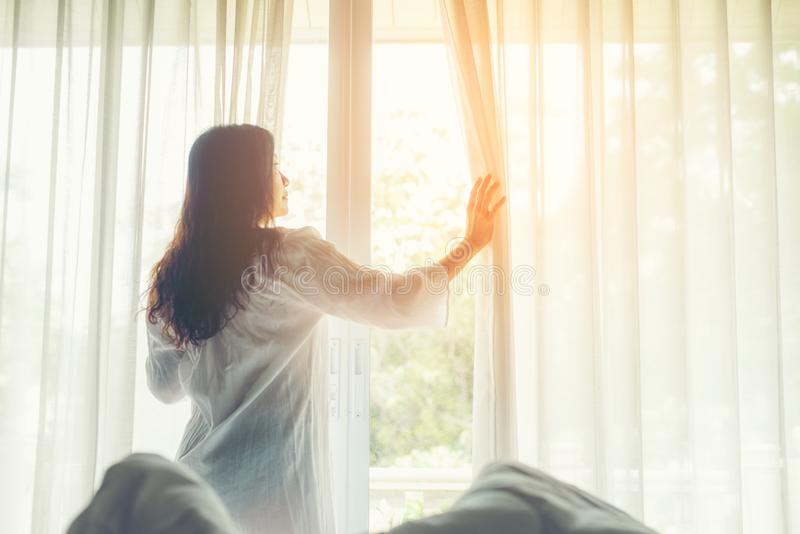 Les femmes de mode de vie ouvrent la fenêtre après pour lever le lit blanc dans le lever de soleil de matin pour détendre l'humeu images libres de droits
