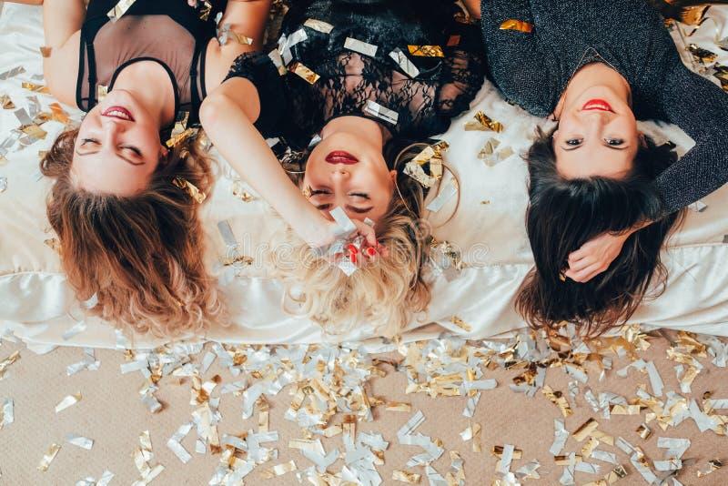 Les femmes de partie reposent des confettis de lit de soulagement de relaxation photo libre de droits