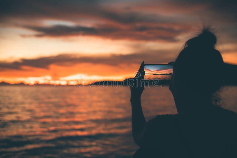 Les femmes de silhouette utilisent le téléphone portable pour la prise un paysage marin de pousse avec le coucher du soleil photos stock