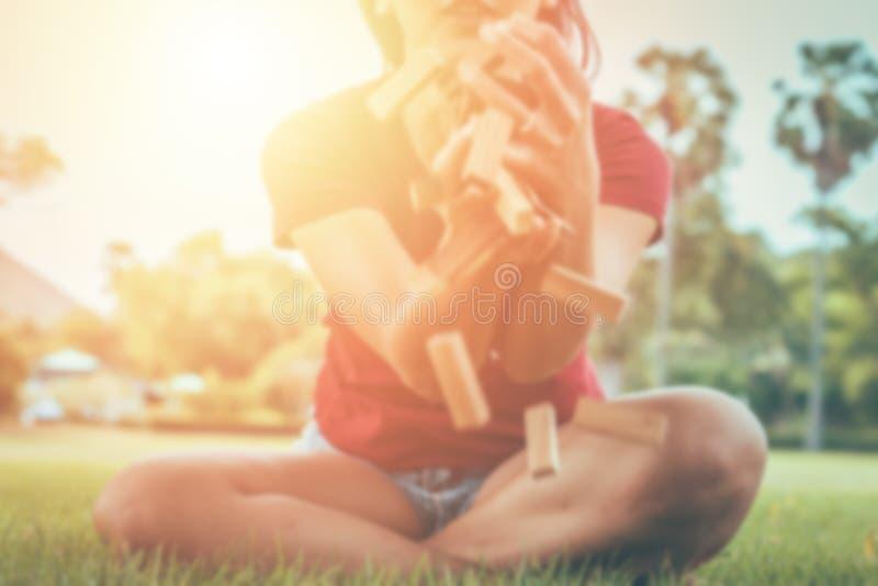 Les femmes de tache floue essayent d'attraper le jouet en bois dans le ciel, le concept pour le défi et l'échouer dans les affair photo stock