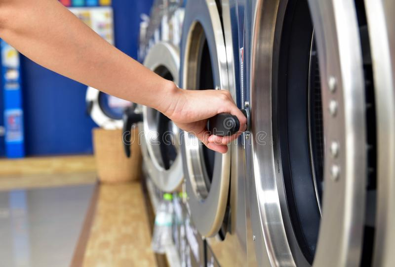Les femmes disposent d'un lave-linge ouvert à la main dans la laverie en libre-service photos stock