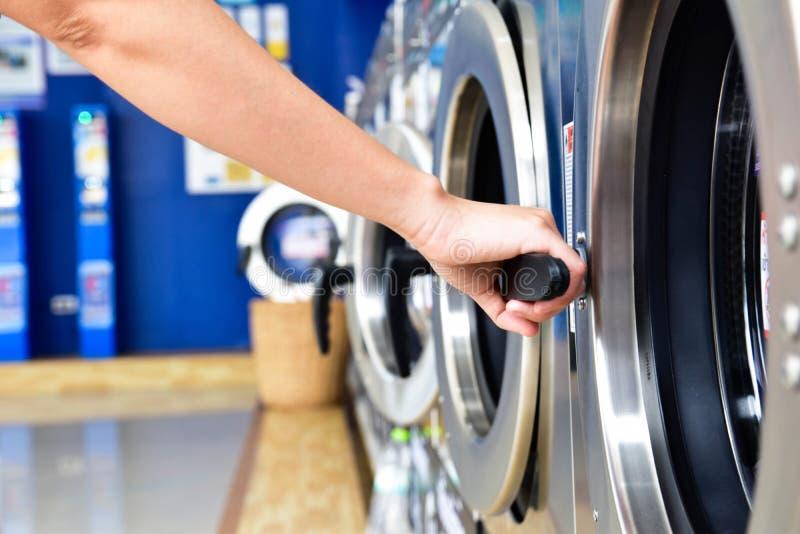Les femmes disposent d'un lave-linge ouvert à la main dans la laverie en libre-service photographie stock