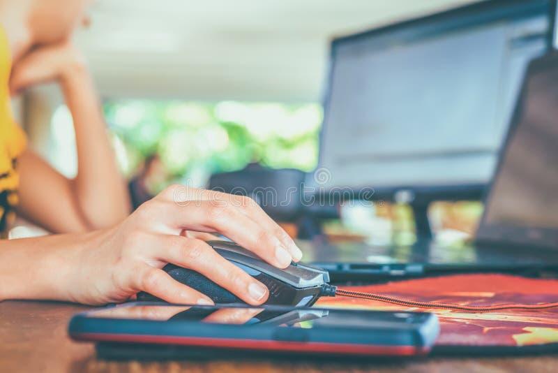 Les femmes emploient la souris d'ordinateur pour travailler à la table images stock