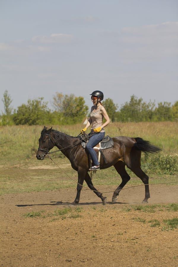 Les femmes est l'équitation - fille rouge de cheveux dans le pré d'été photos stock