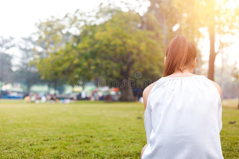 Les femmes est sur l'herbe et beau elle lisant un livre images libres de droits