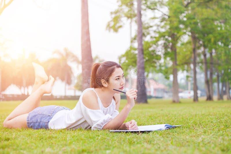 Les femmes est sur l'herbe et beau elle lisant un livre photos libres de droits