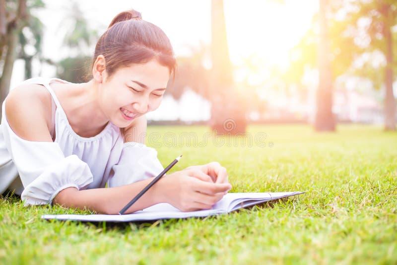Les femmes est sur l'herbe et beau elle lisant un livre image libre de droits
