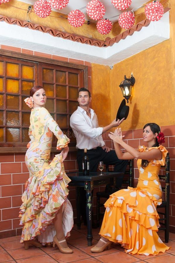 Les femmes et l'homme dans des robes traditionnelles de flamenco dansent pendant Feria de Abril sur April Spain images stock