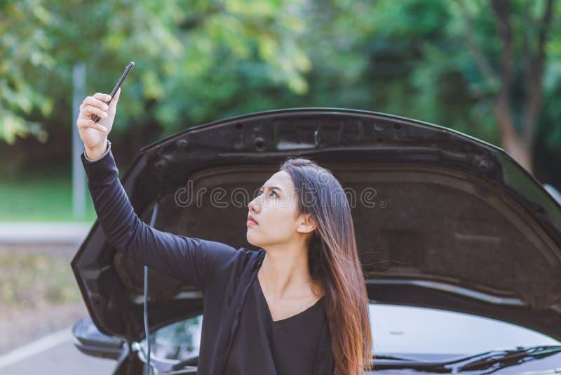 Les femmes et ont décomposé la voiture sur la route et il trouvent le téléphone portable de signal images libres de droits