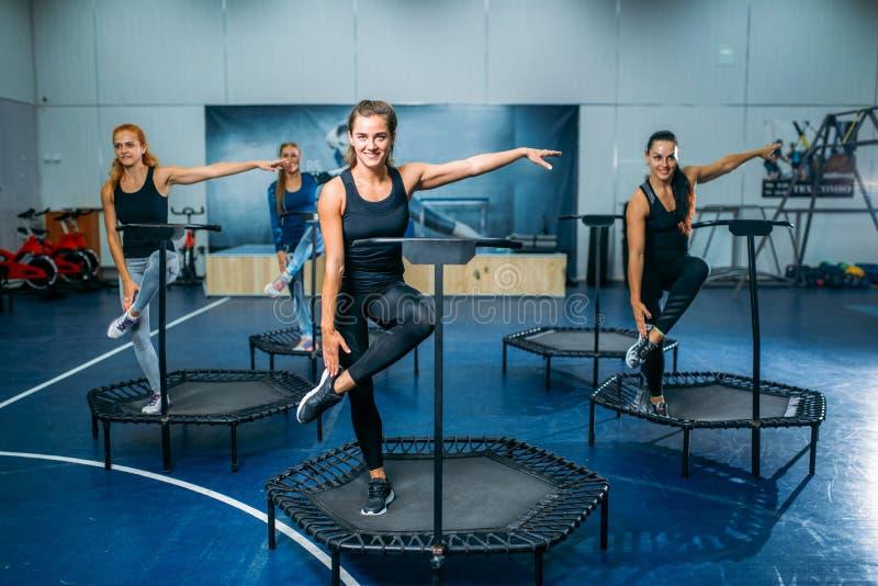 Les femmes groupent faire l'exercice convenable sur le trempoline de sport images libres de droits