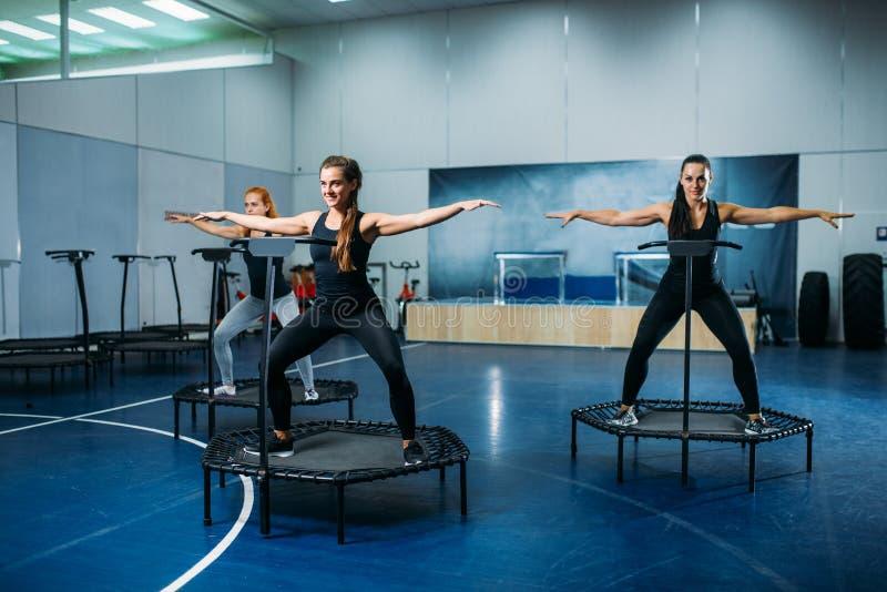 Les femmes groupent faire l'exercice convenable sur le trempoline de sport photos libres de droits