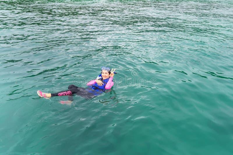Les femmes heureuses pose dans l'eau bleue avec des poissons après avoir navigué au schnorchel, jour d'été photos libres de droits