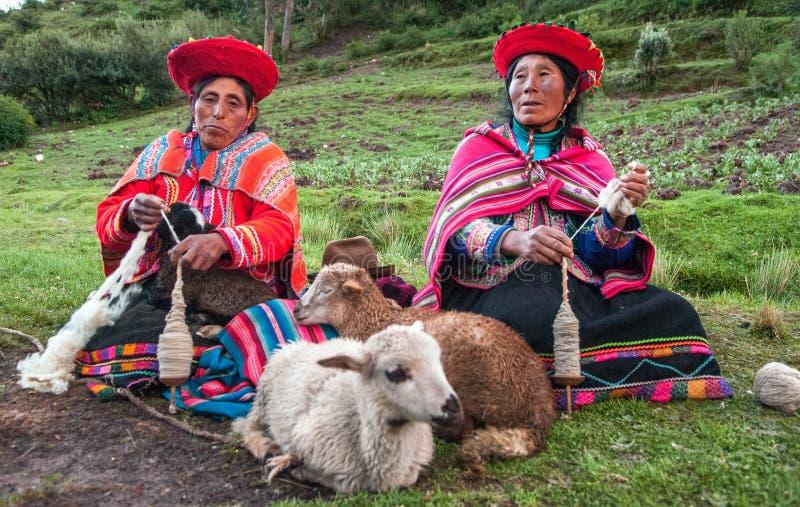 Les femmes indiennes péruviennes dans des vêtements traditionnels tissent un fil, se reposant sur une herbe près des moutons photographie stock libre de droits